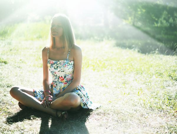 Person sitting on ground in sunlight